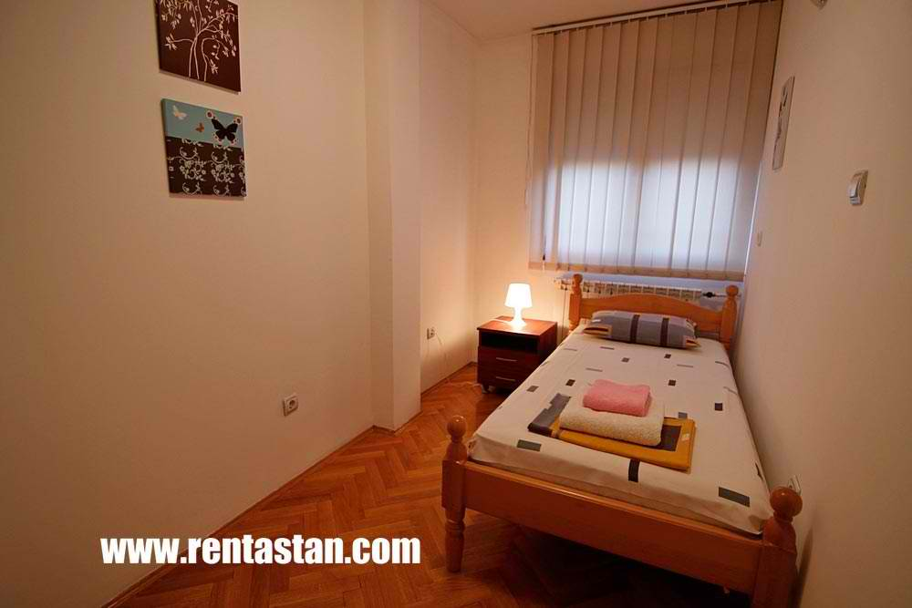Mala spavaća soba sa singl krevetom u apartmanu Aleksandrija